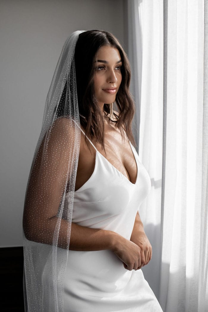 Bride wears Ivory Silver Grace Loves Lace Shimmy Veil while standing in front of curtain