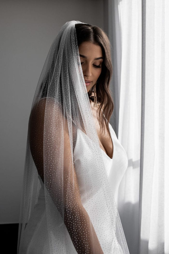 Bride wearing Ivory Silver Grace Loves Lace Shimmy Veil with light filtering through curtain