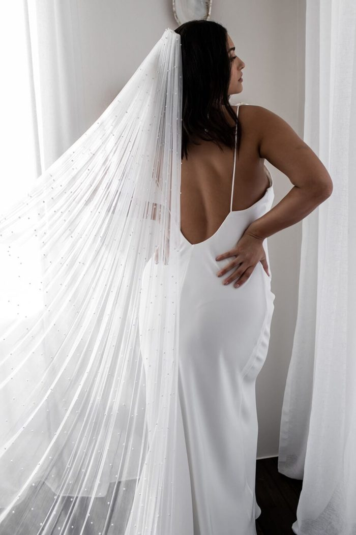 Back shot of bride wearing Grace Loves Lace Pearly Long Veil as it trails behind her