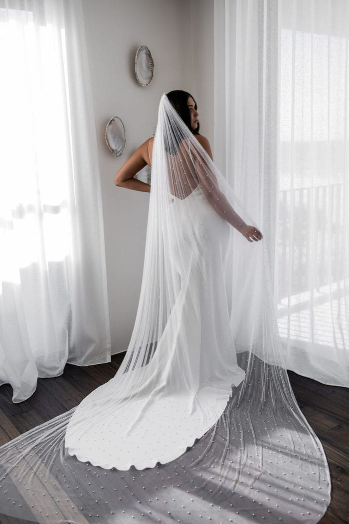 Back shot of bride wearing Grace Loves Lace Pearly Long Veil, holding it out with one hand