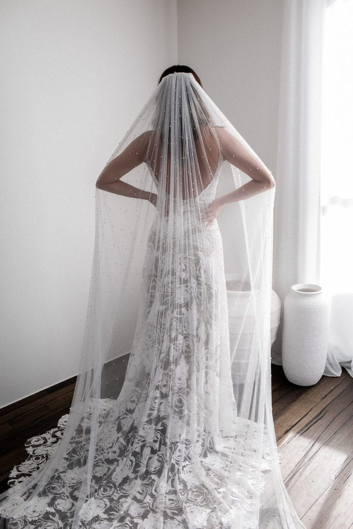 Back shot of bride wearing Grace Loves Lace Pearly Long Veil draping over her shoulders