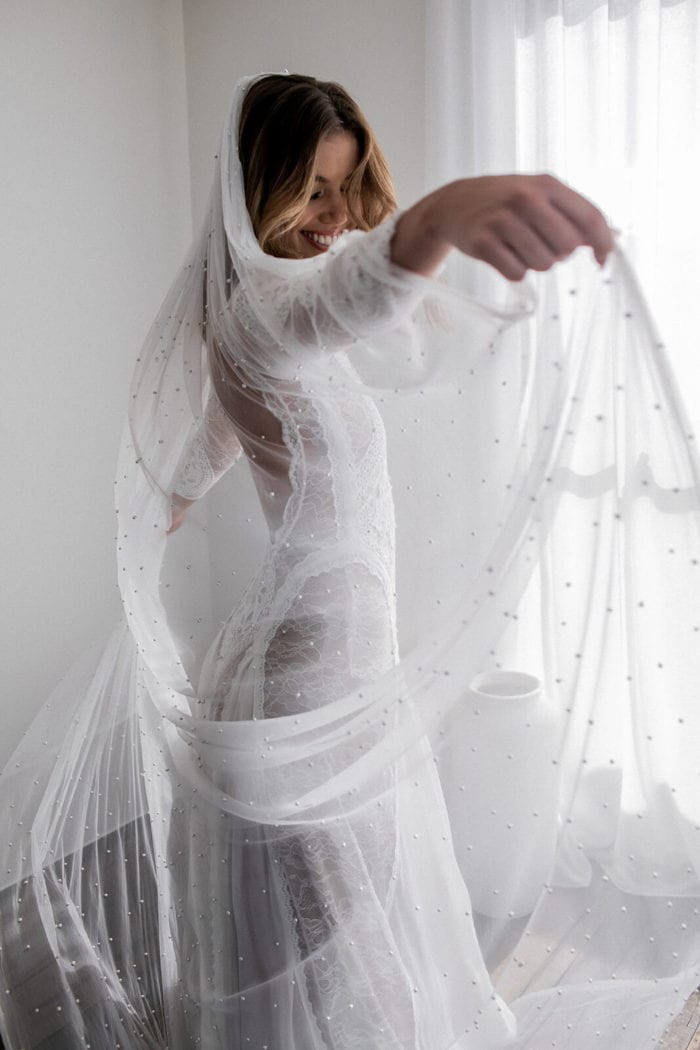Bride wearing Grace Loves Lace Pearly Long Veil as she dances, holding the veil in both hands