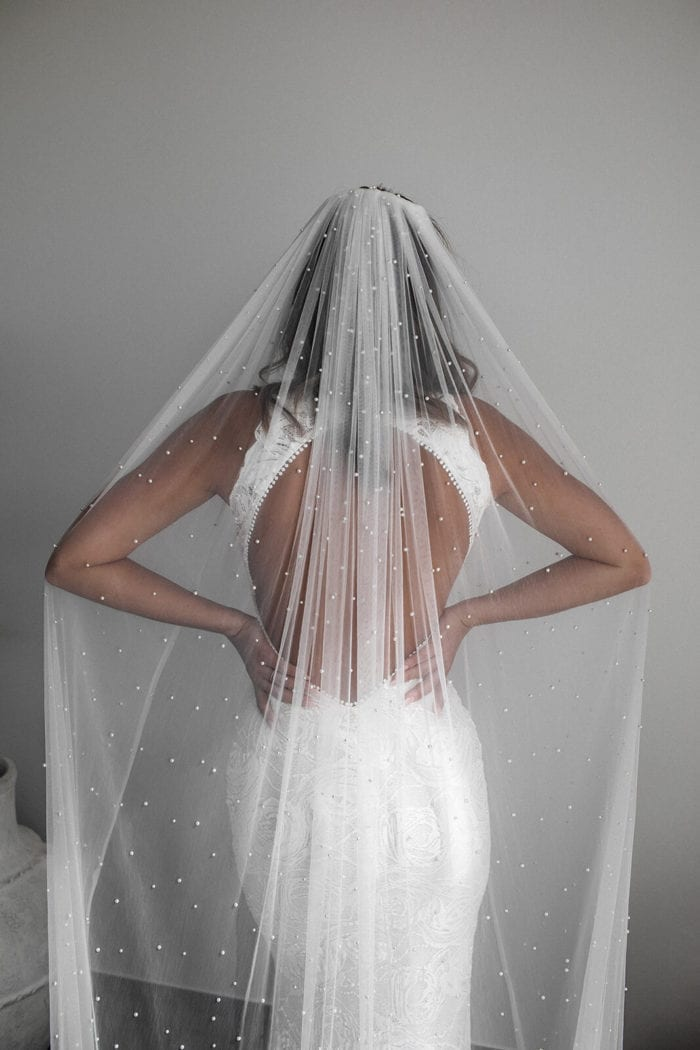 Back shot of bride wearing Grace Loves Lace Pearly Long Veil draped over her shoulders