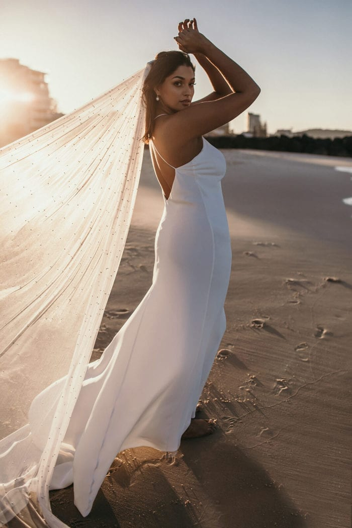 Bride wears Grace Loves Lace Pearly Long Veil while walking along beach barefoot