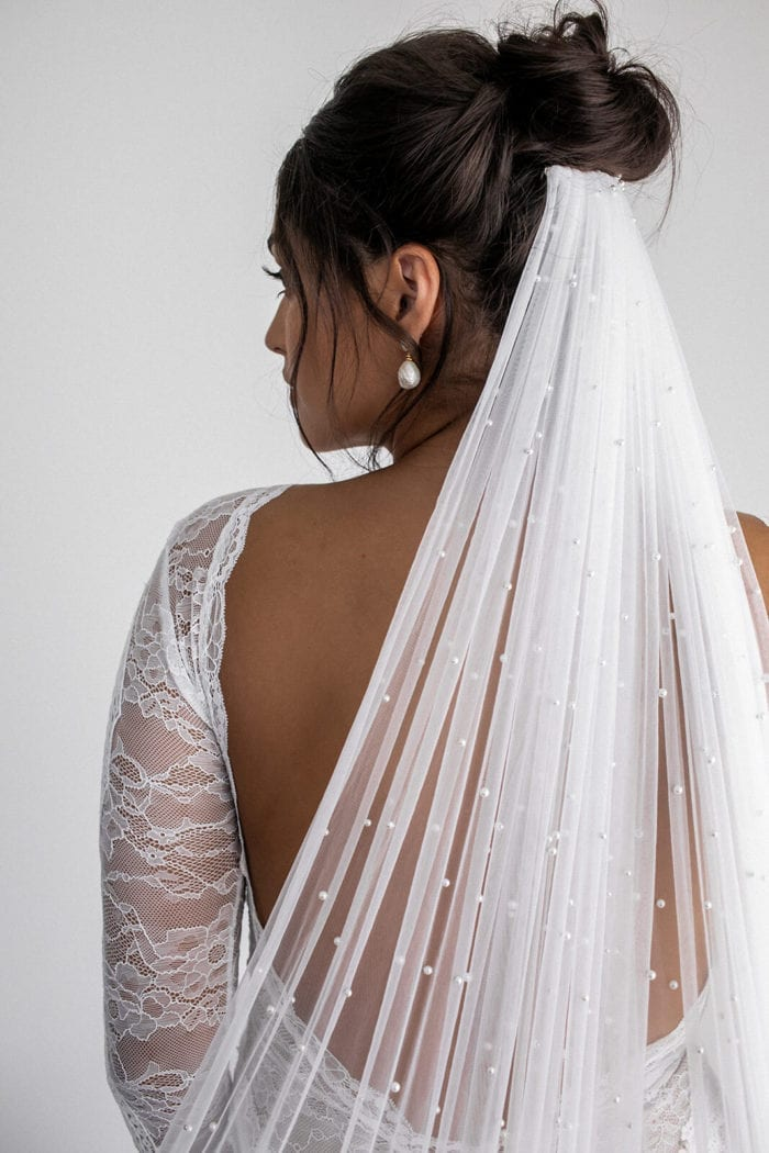 Back shot of bride wearing Grace Loves Lace Pearly Long Veil pinned under high bun