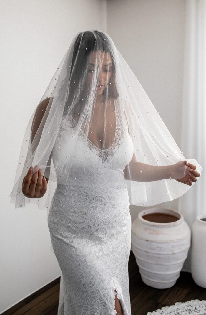 Bride wears Grace Loves Lace Pearly Blusher Veil draped over her face held in both hands
