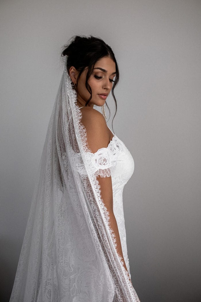 Bride wears Grace Loves Lace Chantilly Veil while looking downward