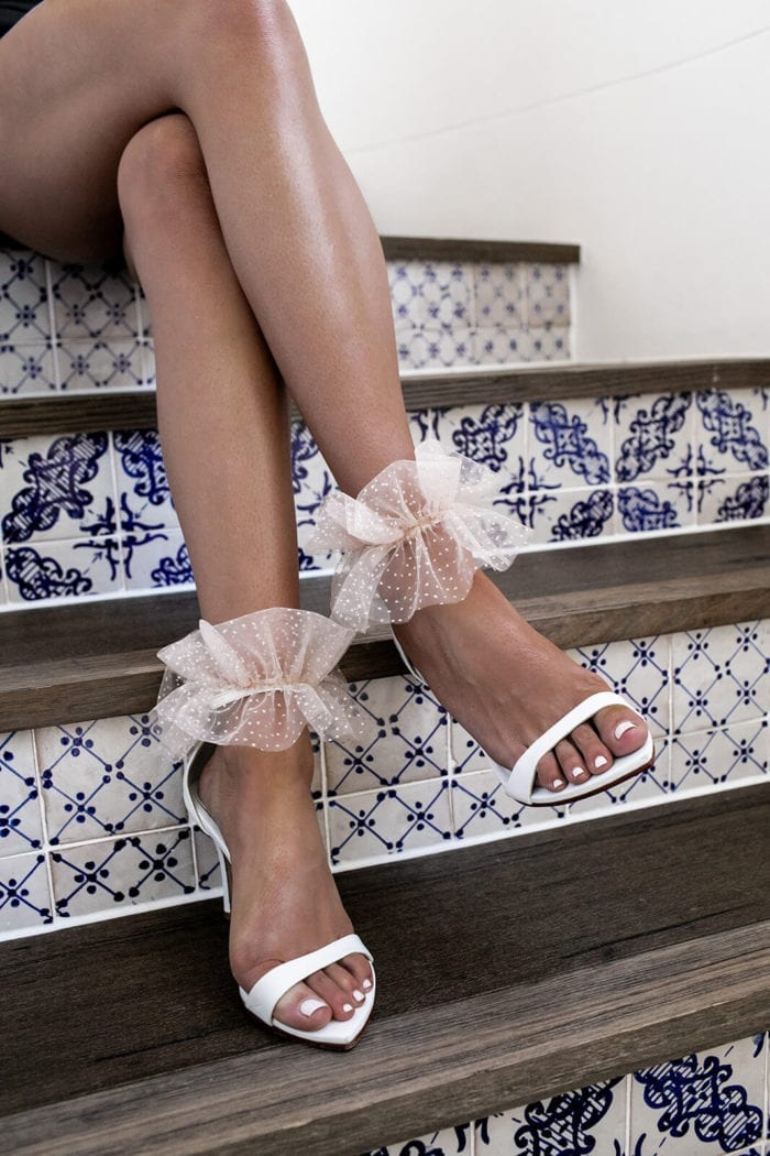 Bride wearing Grace Loves Lace Shimmy Anklets sitting on stairs