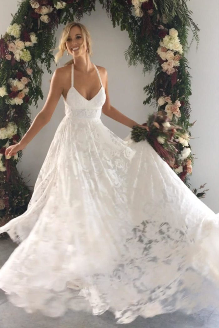 Blonde bride wearing Grace Loves Lace Megan Gown holding skirt and bouquet in one hand