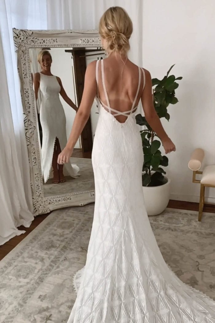 Back shot of blonde bride wearing Grace Loves Lace Leon Gown looking in mirror