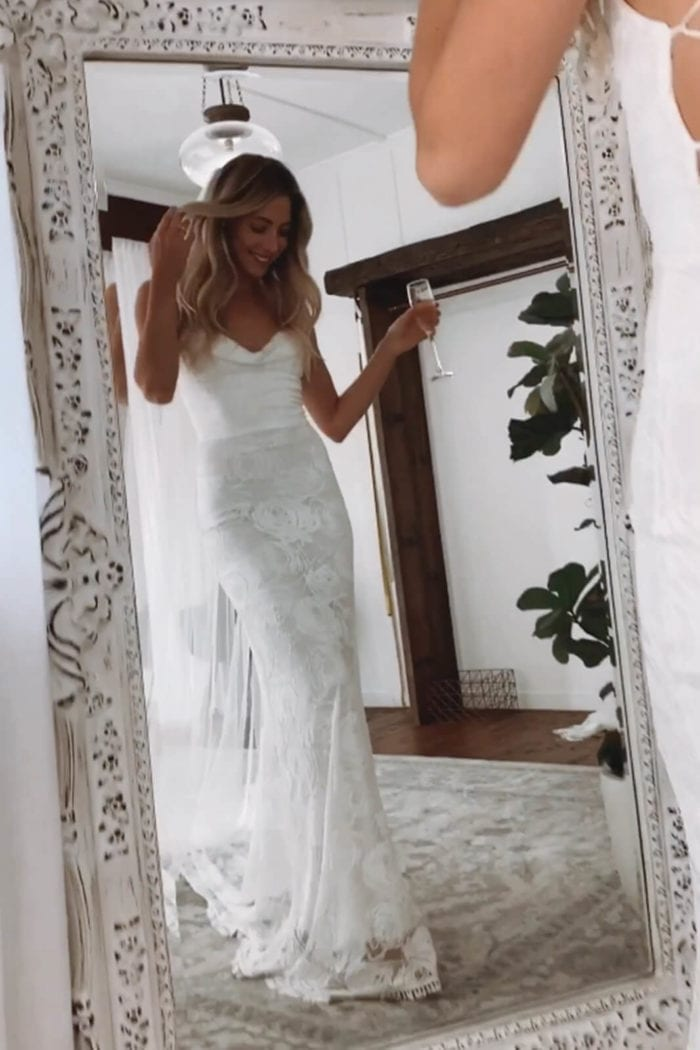 Blonde bride wearing Grace Loves Lace Honey Rose Gown holding champagne glass in mirror