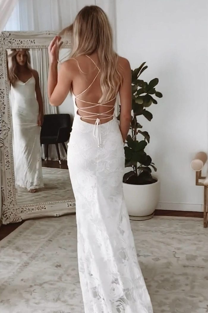 Back shot of blonde bride wearing Grace Loves Lace Honey Rose Gown looking in mirror