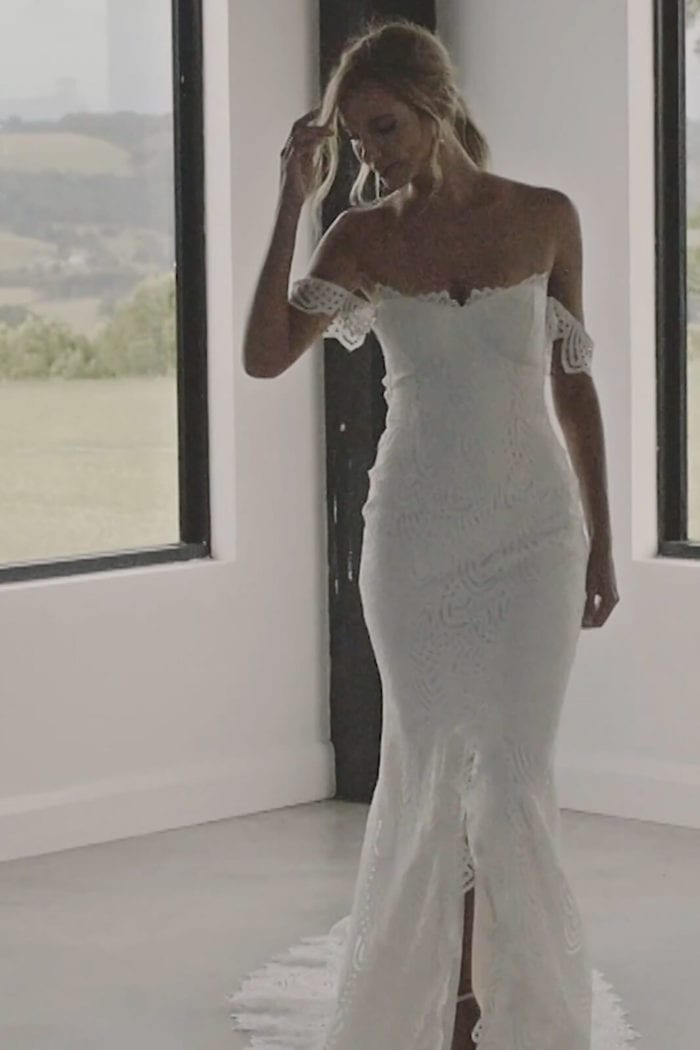 Blonde bride wearing Grace Loves Lace Paloma Gown with hand on hair