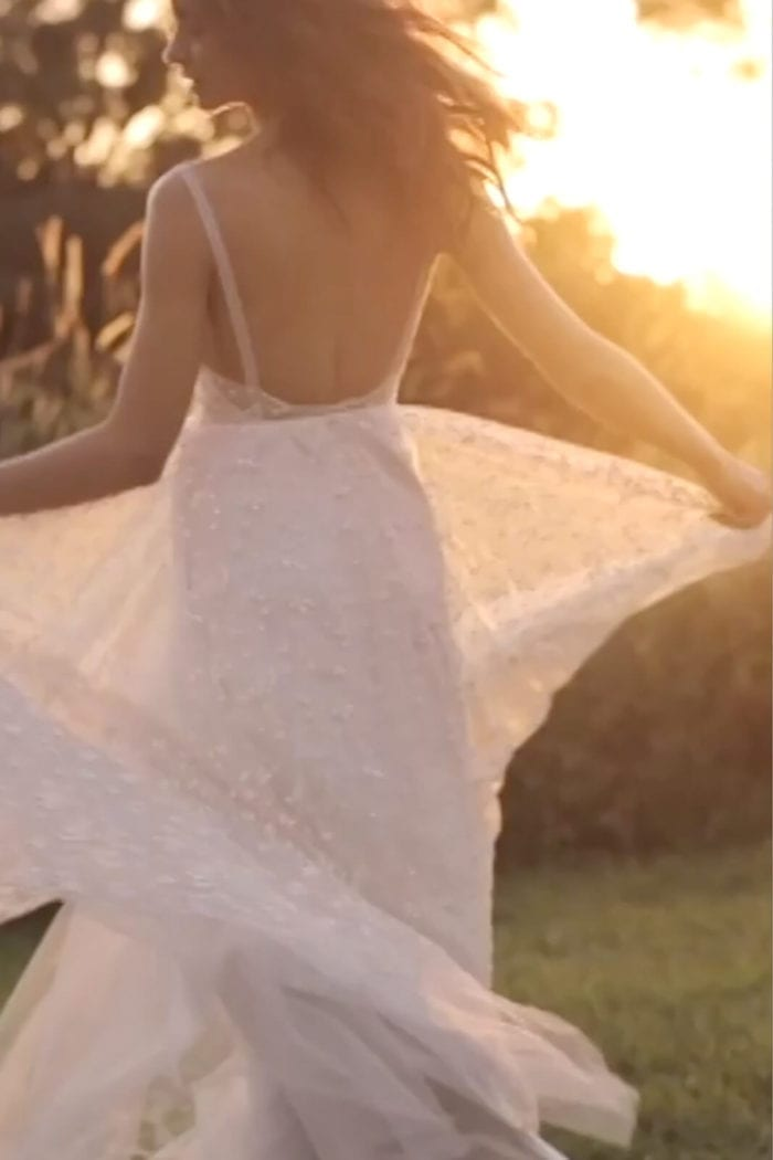 Back shot of bride wearing Grace Loves Lace Menha Gown holding skirt in hands
