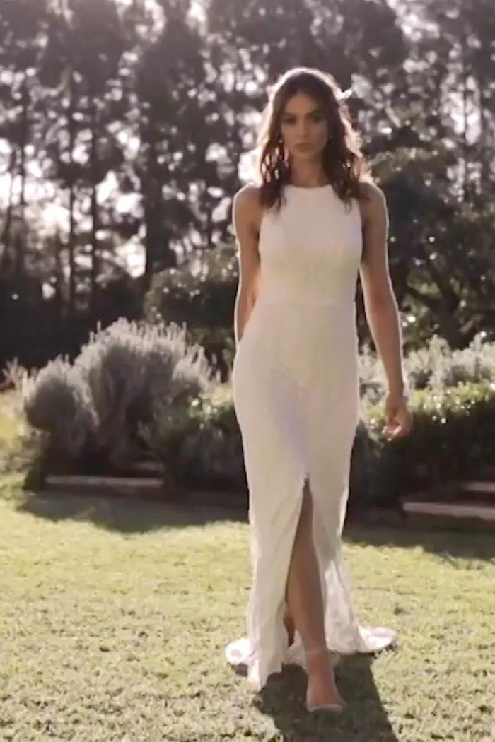 Brunette bride wearing Grace Loves Lace Leon Gown walking on grass