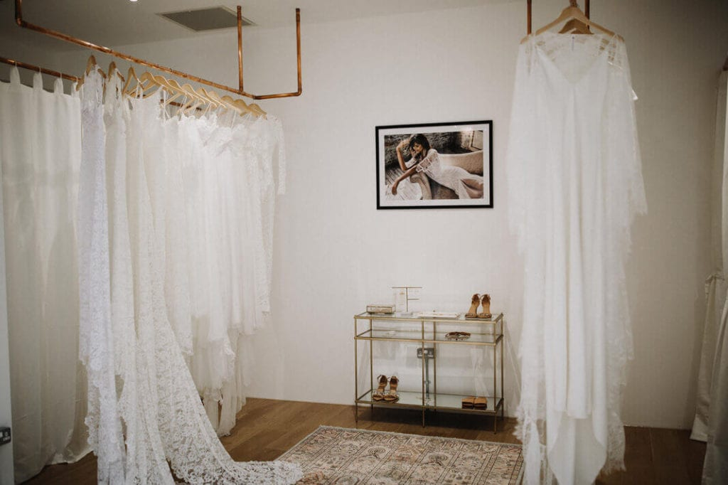 Lace wedding gowns hanging from a ceiling mounted rack in a change room
