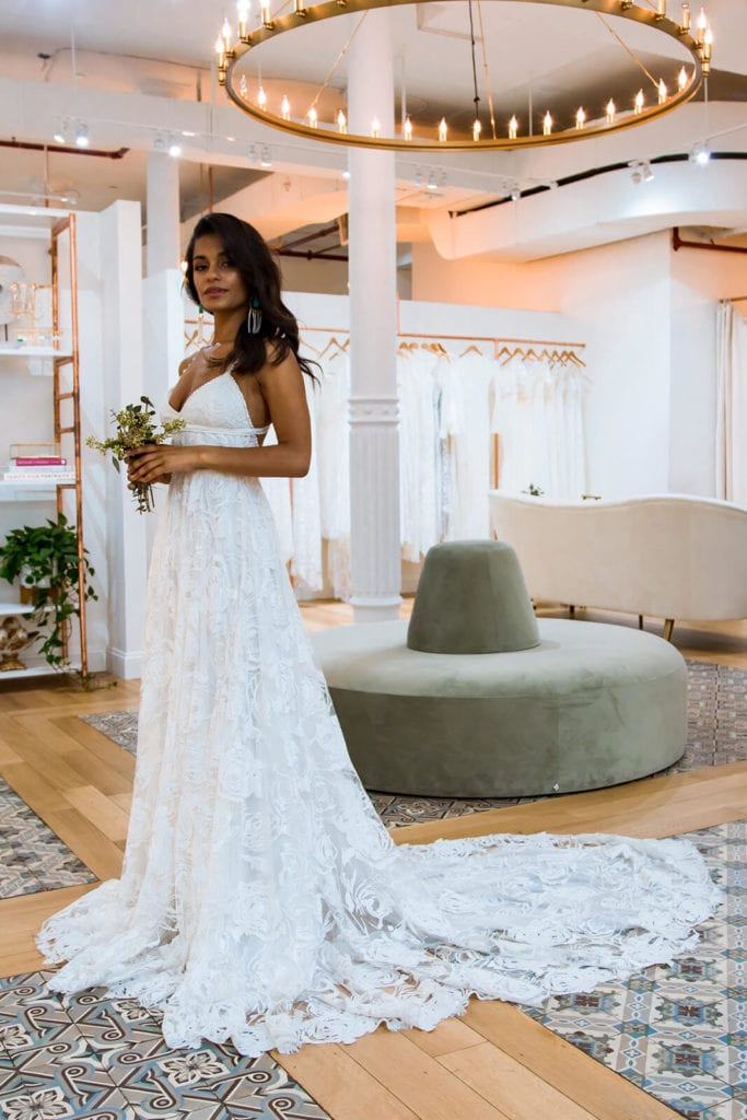 Side view of bride wearing a lace wedding gown with long train and lounges behind her