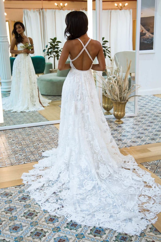 Back view of bride trying on wedding gown while looking in a large mirror