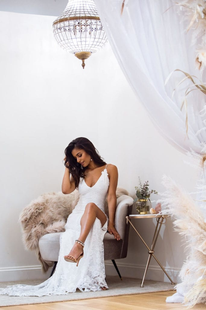 Bride wearing lace gown sitting on single seater lounge chair with crossed leg looking down