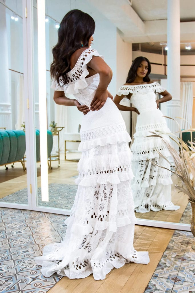 Back view of bride facing a large mirror arching herself backwards