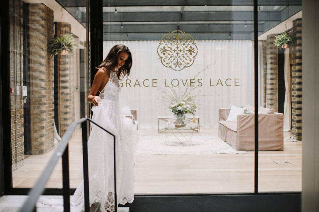 Side view of bride wearing a lace wedding dress walking down a small set of stairs at the front of our London wedding gown showroom