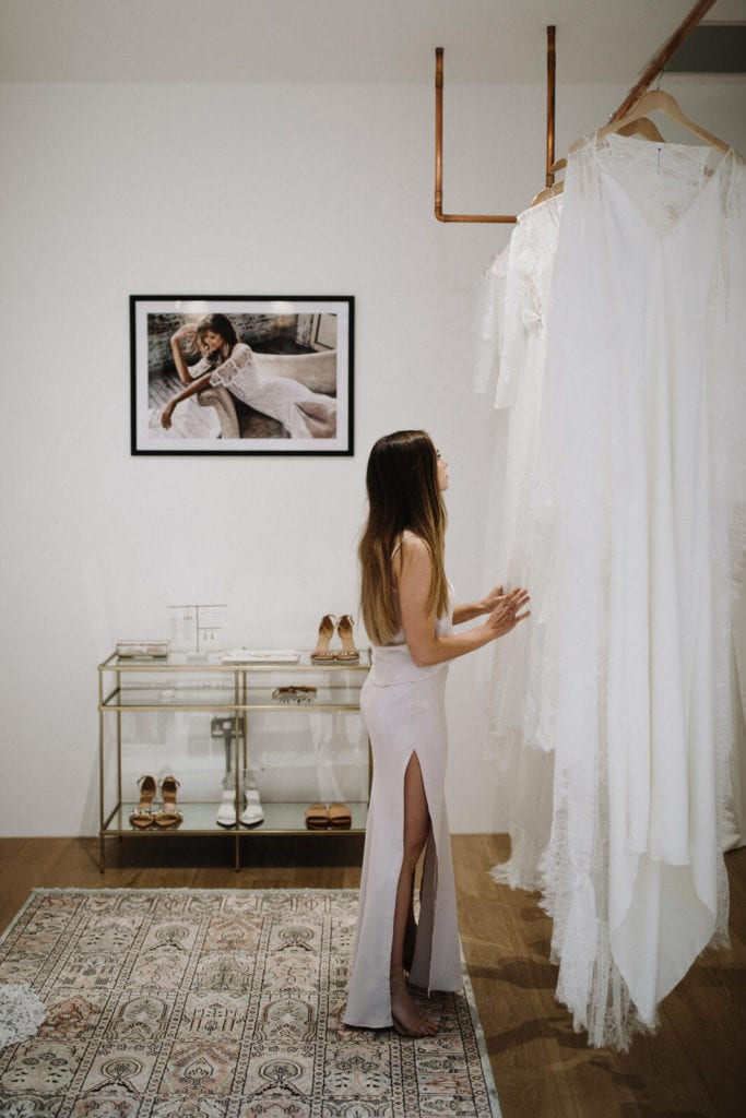 Side view of bride wearing a lace dress and leg split looking through other wedding gowns hanging on a rack