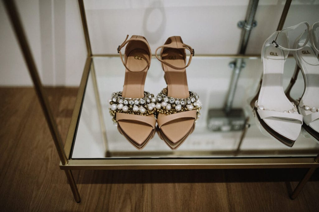 Bride shoes in a glass display cabinet with metal frame