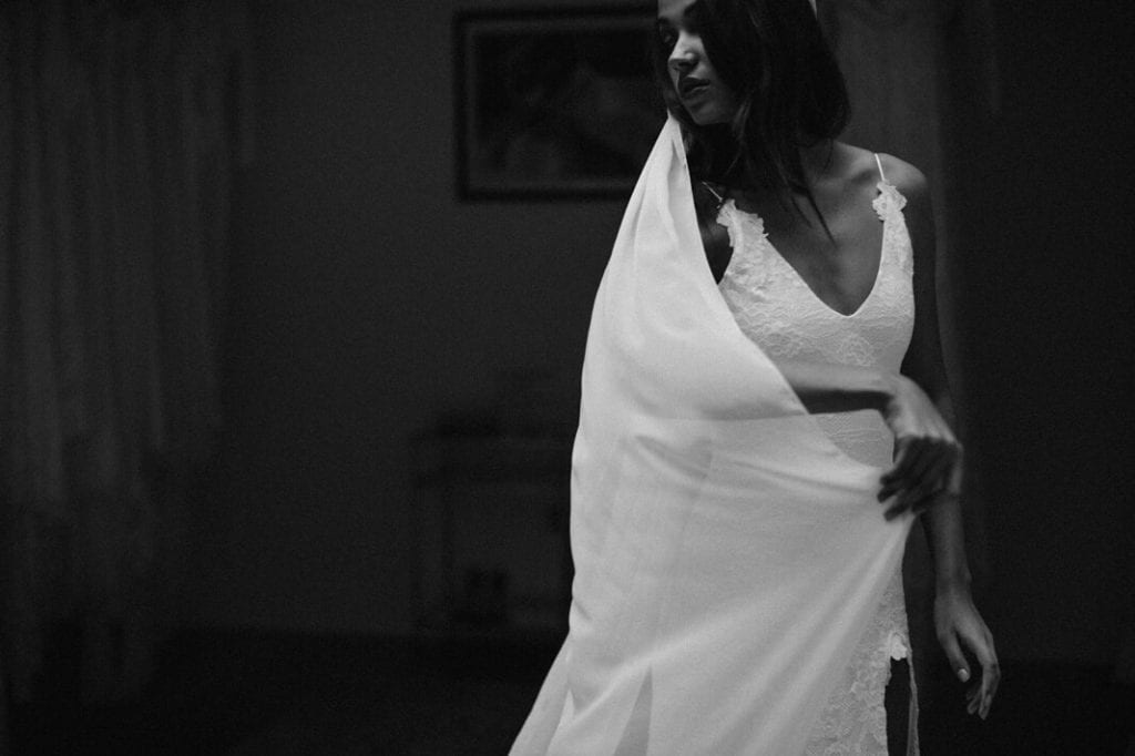 Black and white image of bride wearing wedding dress and veil
