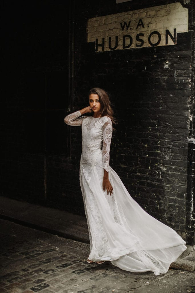 Bride wearing a lace wedding gown standing outside in front of a dark brick wall