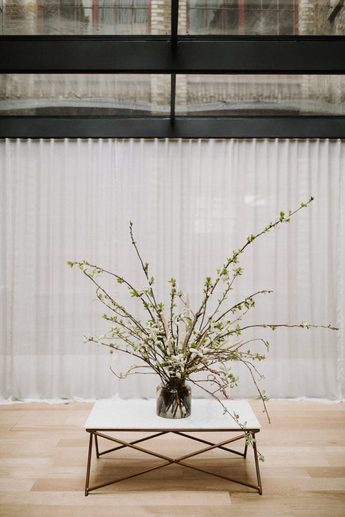 Feature plant arrangement on white table in front of white sheer curtains in our wedding gown showroom in London