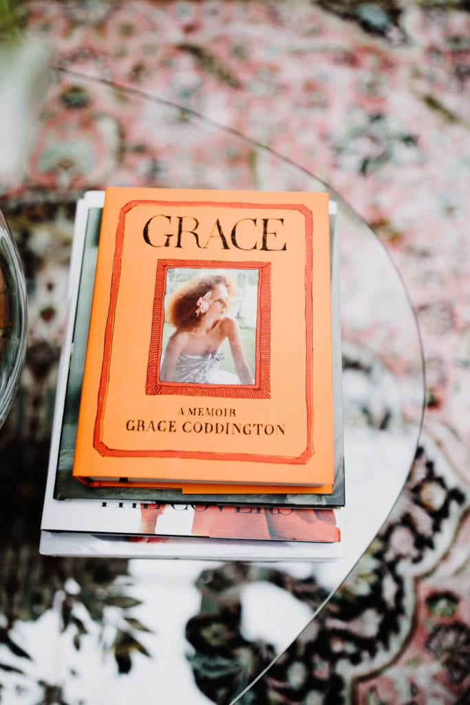 Decorative stack of books with the top book cover word GRACE on an orange background