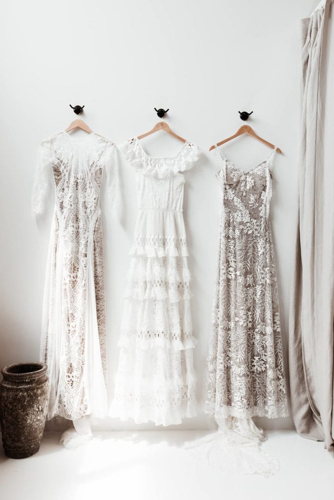 Three elegant lace wedding gowns hanging on a wall in our wedding dress showroom in Dallas