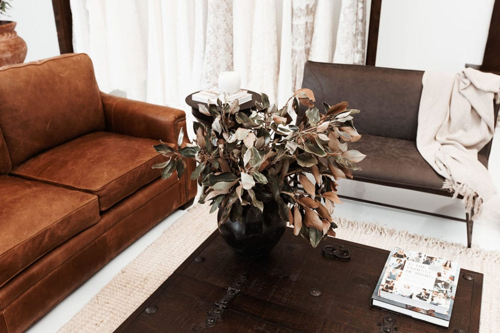 Brown lounges and coffee table featuring dry flower arrangement in a dark pottery vase