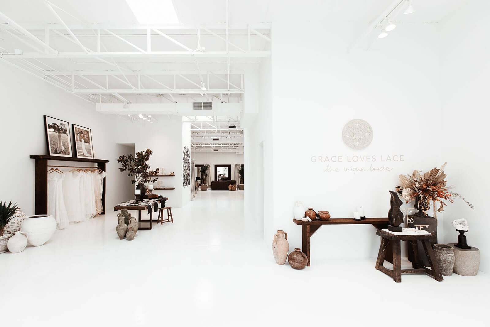 Light and open wedding gown showroom in Dallas with dark timber tables and stool