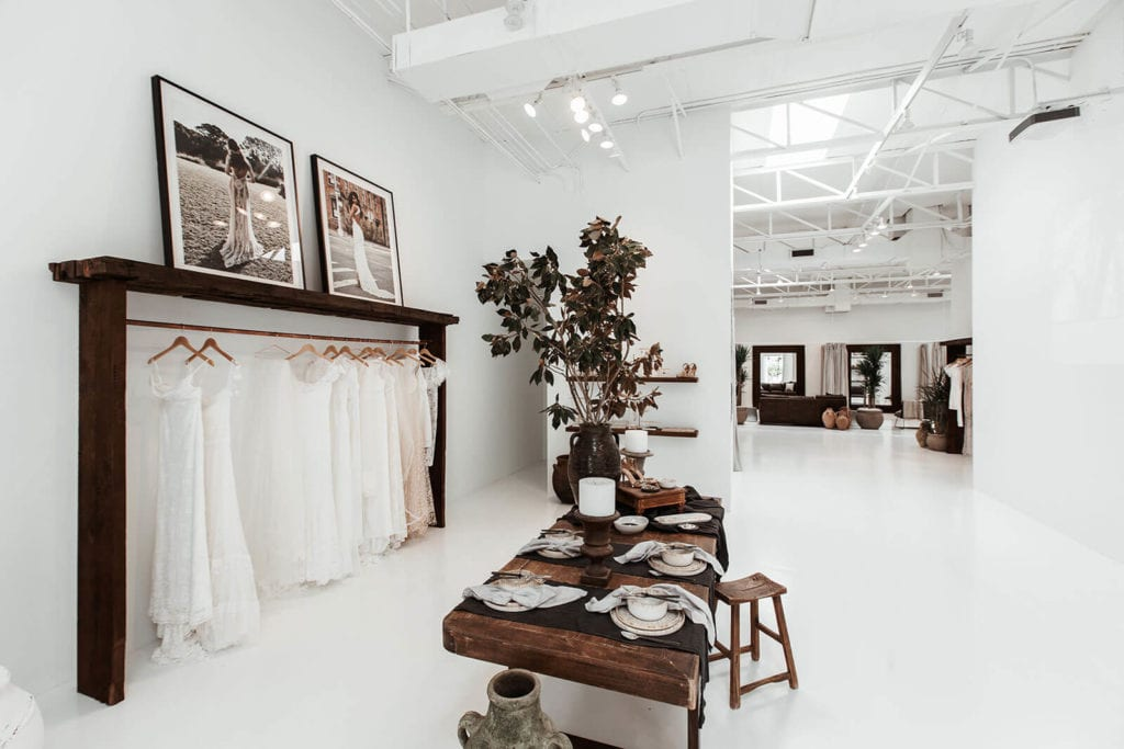 View of wedding gowns on a rack along a wall with a dark wood table covered with accessories opposite