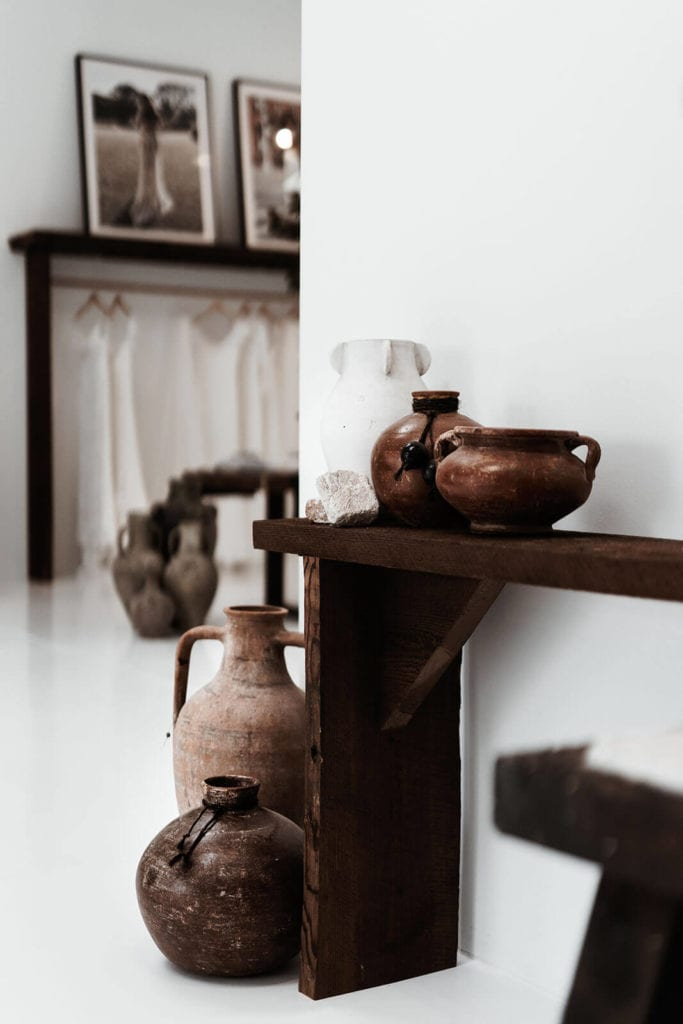 Dark wood shelf on the wall holding decorative pottery in our bridal gown showroom entrance