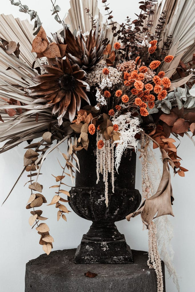 Dried flower arrangement in a black glossy vase standing on a pillar