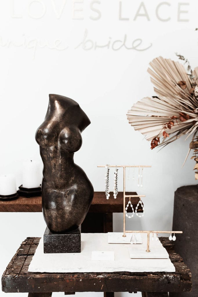 Bronse color bust sculpture beside elegant bridal earrings on a stand in our New York showroom