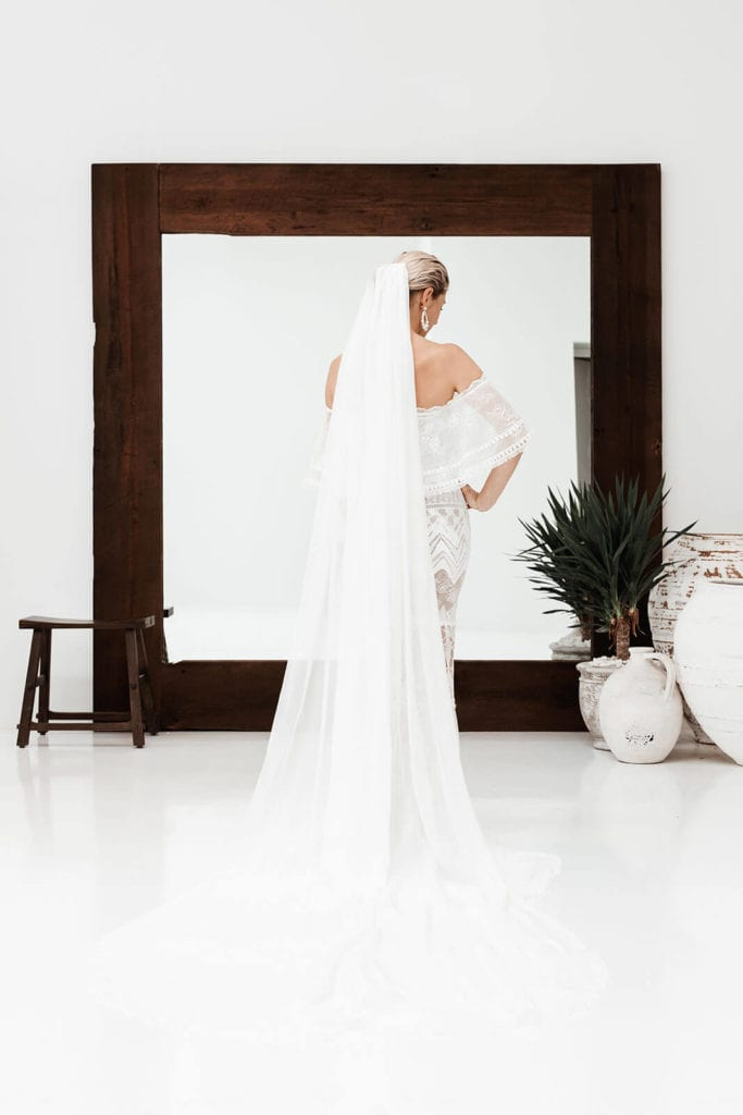 Back view of lace bridal gown and long veil in front of a large floor standing mirror with dark wood frame