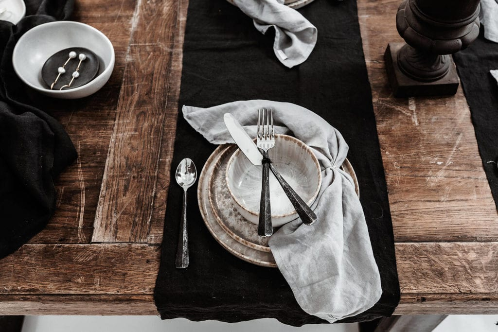 Tea cup and plate with cutlery setting and linen napkin as table decoration in our showroom