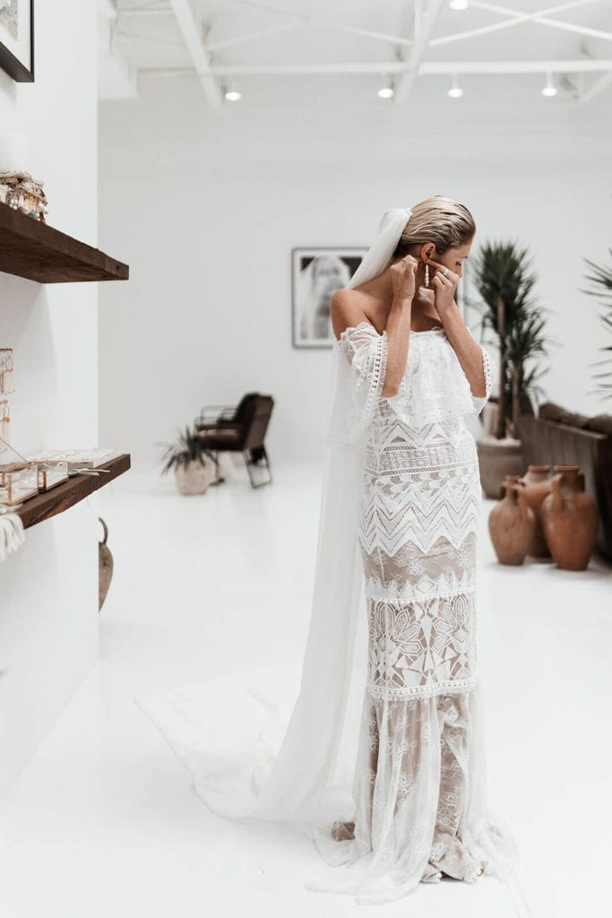 A bride is adjusting her earrings while trying on her elegant wedding dress in our New York bridal gown showroom