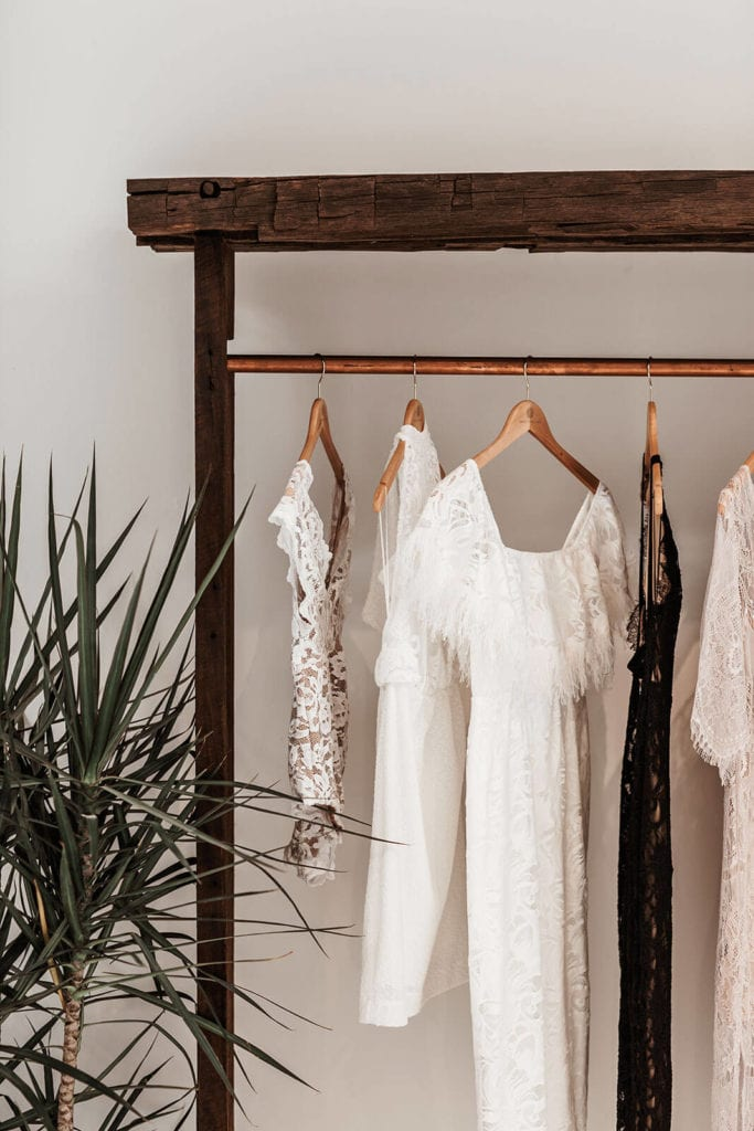Lace wedding gowns on wood hangers near a plant in our showroom in New York