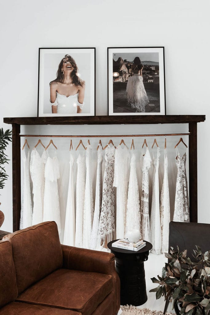 Bridal gowns hanging on a rack under a shelf holding framed photo prints of more wedding dresses