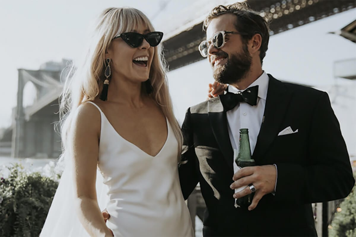 Blonde bride wearing Grace Loves Lace Arlo Gown wearing sunglasses standing with groom holding beer bottle and wearing sunglasses