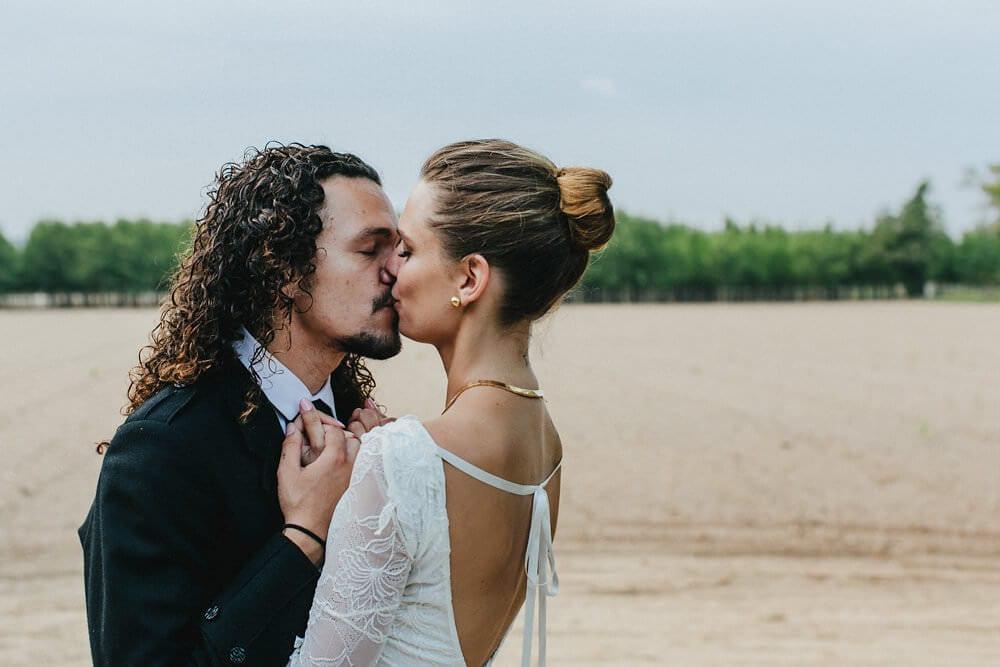 Brunette bride wearing Grace Loves Lace Francis Gown kissing groom