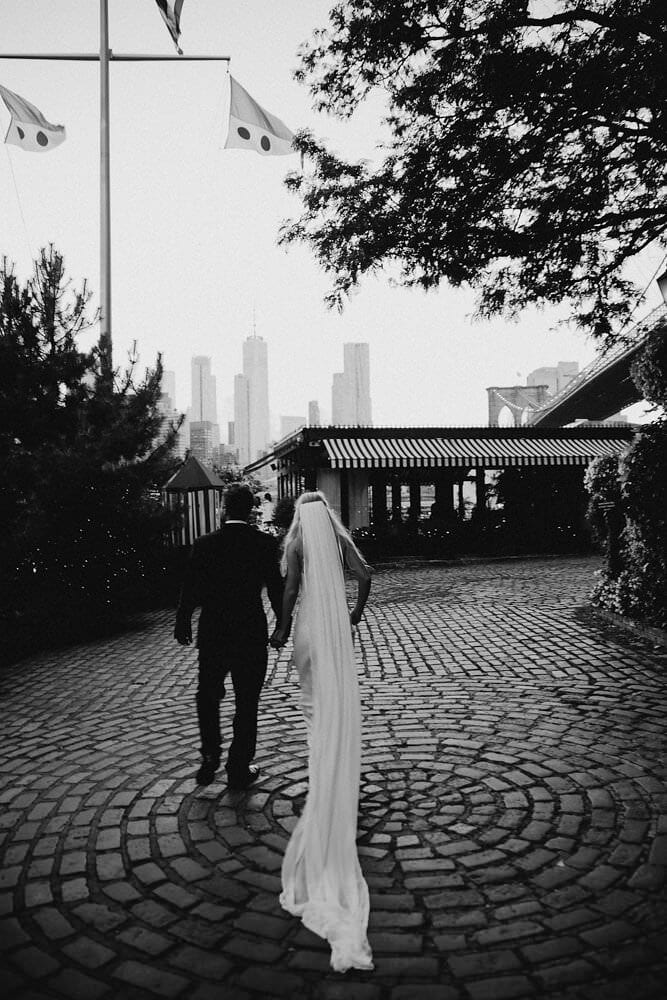 Black and white shot of bride wearing Grace Loves Lace Arlo Gown holding hands with groom in empty plaza