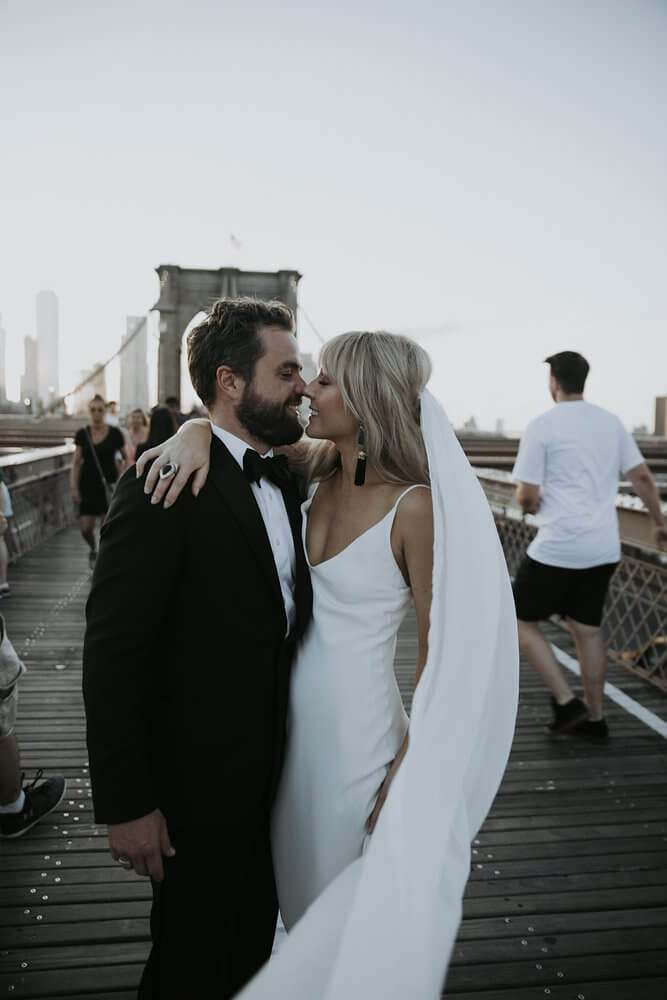 Blonde bride wearing Grace Loves Lace Arlo Gown embracing groom touching noses on pedestrian bridge