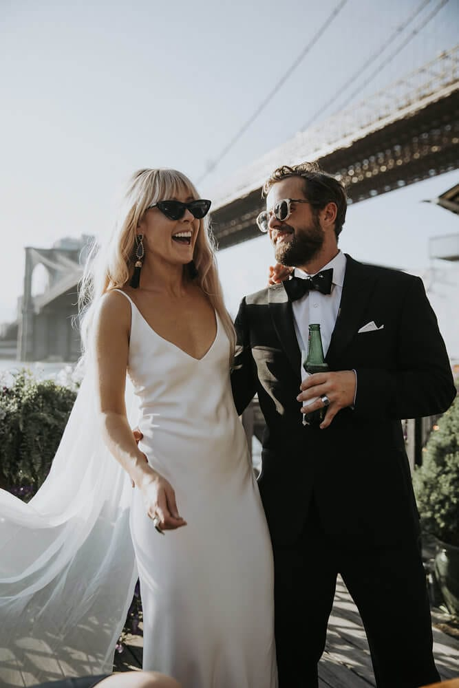 Blonde bride wearing Grace Loves Lace Arlo Gown and sunglasses standing with groom wearing sunglasses and holding a beer bottle
