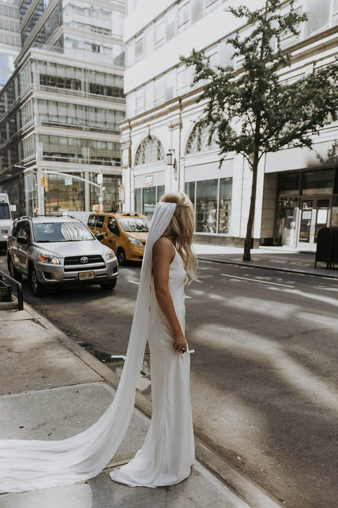 Blonde bride wearing Grace Loves Lace Arlo Gown standing beside road holding skirt