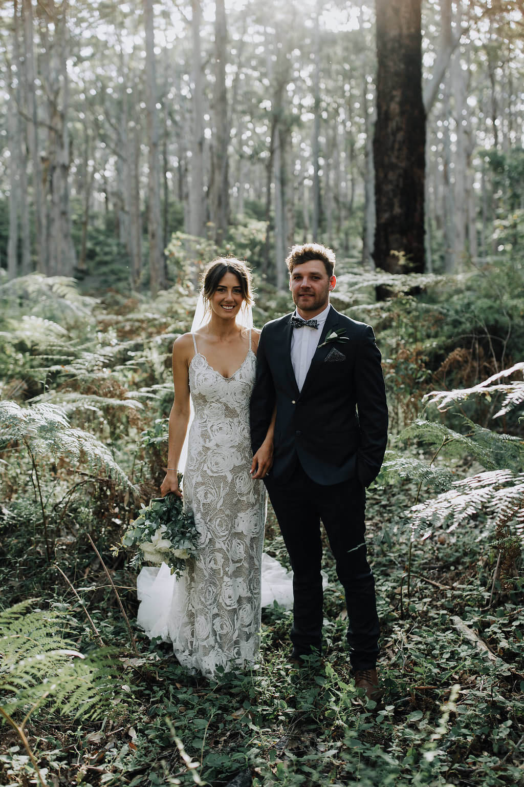 Bride wearing Grace Loves Lace Rosa Gown holding train with groom in forest